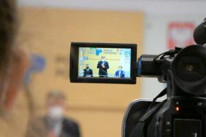 Zdjęcie ekranu kamery rejestrującej obraz podczas podpisywania umów z Metropolią Poznań