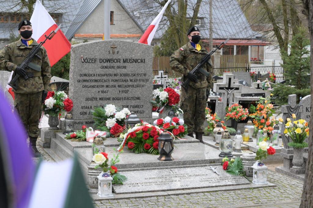 Na zdjęciu grób Józefa Dowbor Muśnickiego, przy którym stoi dwóch żołnierzy z bronią w ręku.