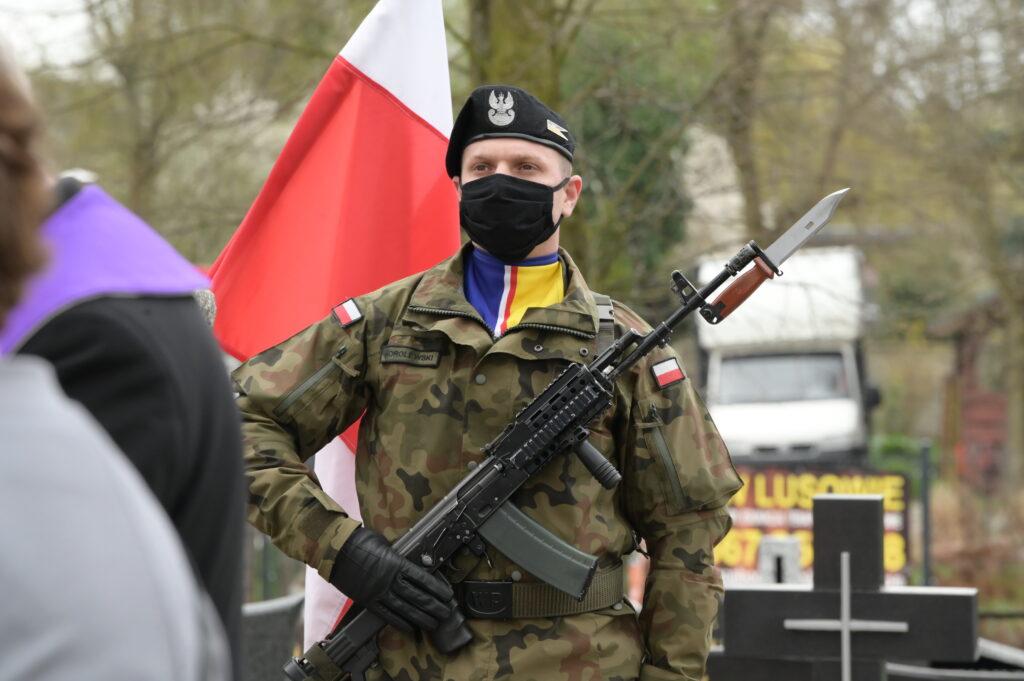 Na zdjęciu żołnierz z bronią, a przy nim powiewająca biało-czerwona flaga.