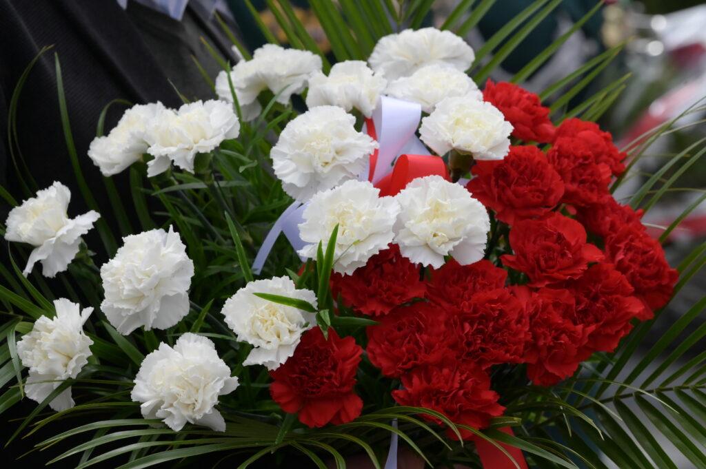 Na zdjęciu wiązanka biało-czerwonych kwiatów.